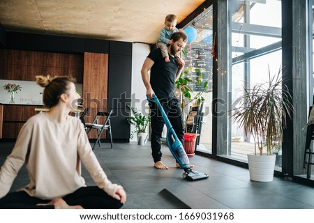 Mother sits at easy simplified lotus pose, looking at the father vacuum cleaning apartment floor with their infant baby riding on his neck