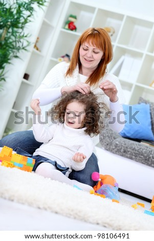 Mother sitting on floor and brushing her daughter's hair