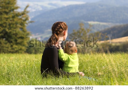 Mother sitting with child on meadow in mountains summer