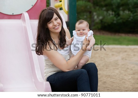 Mother sitting with her adorable daughter in playground