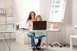 Mother sitting with her daughter on her lap at a table in a home classroom teaching her on a laptop computer