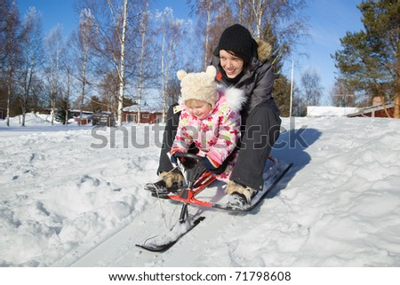 Mother sledding with her daughter in winter