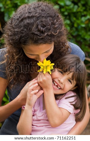 Mother smelling a flower with her daughter