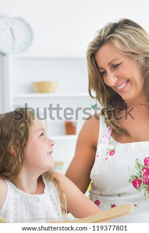 Mother smiling at her daughter during preparing salads