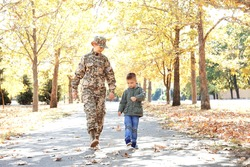 Mother soldier and little kid walking in the park
