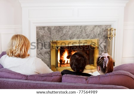 Mother son and daughter sit on the sofa  to read by the fire