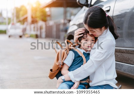 Mother soothe a son crying and sending to school, Parent and pupil going to kindergarten of preschool first day back to school concept.