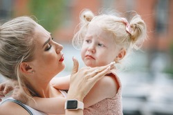 Mother soothes her crying blonde daughter. Mom holds the girl in her arms and wipes away her tears.