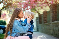 Mother soothing her sad child outdoors. Mom with upset baby on a walk at spring. Toddler boy crying at street. Motherhood, family and lifestyle. Family outdoors. Mother hugging her sad son.