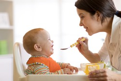 Mother spoon feeding her baby boy. Side view portrait of young woman giving food to kid son