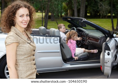 Mother stands half-turned near an open top car, children play inside the car