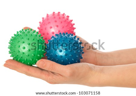 Mother stretches three colored massage balls for the children's hands development to her baby