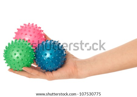 Mother stretches three colored massage balls for the children's hands development to her baby - stock photo