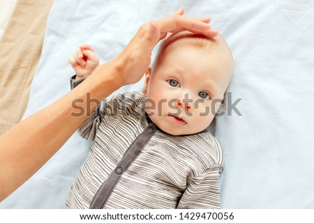 Mother stroking the child to feel the fontanel of 3 months baby boy #1429470056