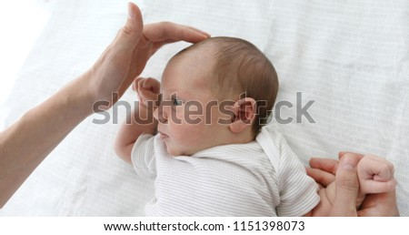 Mother stroking the child to feel the fontanel of 1 months baby girl #1151398073
