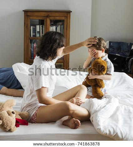Mother taking care of sick child in bed