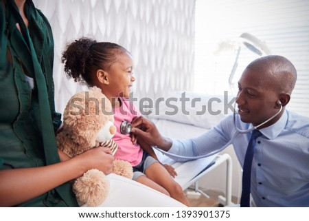 Mother Taking Daughter For Medical Exam In Doctors Office