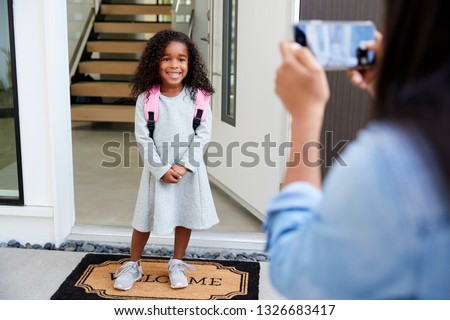Mother Taking Photo Of Daughter With Cell Phone On First Day Back At School