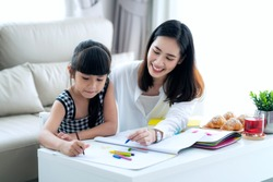 Mother teach Asian preschool student do homework by reawing by a color, this image can use for girl, study, school,mother, teacher, kid, student and education concept