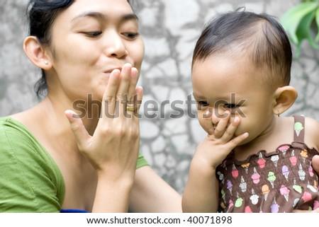 mother teach her baby girl a goodbye kiss