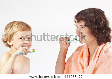 Mother teaches her child to brush their teeth on a white background