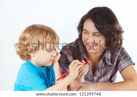 Mother teaches her child to draw with color pencils on a white background