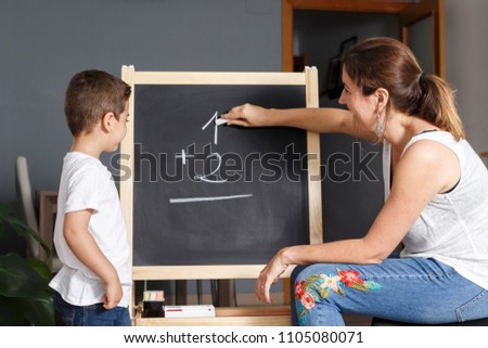 Mother teaches her son math at home with a blackboard