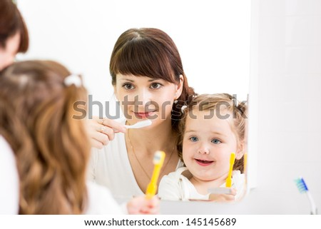 mother teaches kid teeth brushing - stock photo