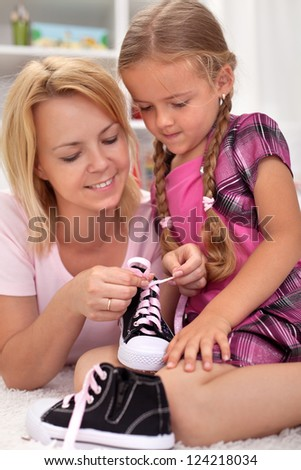 Mother teaching child how to tie shoes - showing the steps