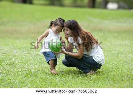 Mother teaching daughter to soccer/ball in the park happily.