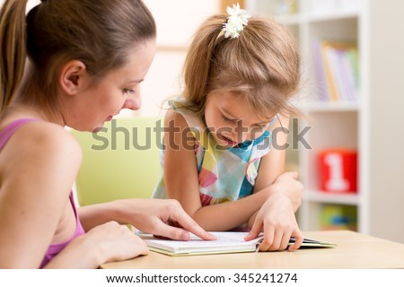 Mother teaching her child daughter to read