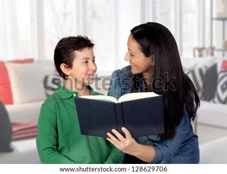 Mother teaching her child to read at home - stock photo