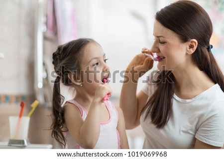 mother teaching kid daughter teeth brushing in bathroom