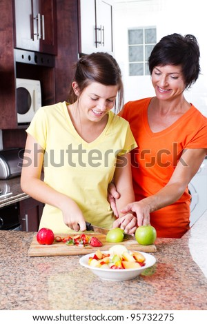 mother teaching teen daughter making fruit salad