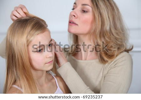 Mother treating daughter's hair against lice