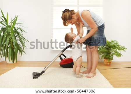 Mother trying to clean the floor while she's baby is crying and wants to be picked up