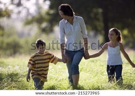 Mother walking hand in hand with son (6-8) and daughter in field, front view