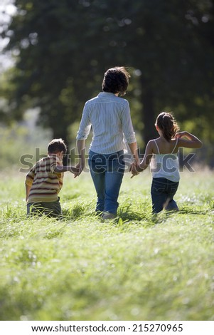 Mother walking hand in hand with son (6-8) and daughter in field, rear view