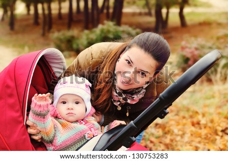 mother walking in the park with her baby in stroller