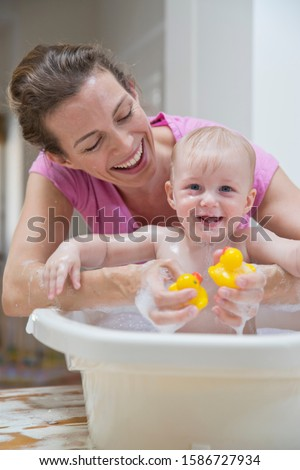 Mother Washing Baby Son In Plastic Bath On Nursery Table