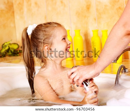 Mother washing child in bubble bath. - stock photo