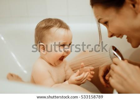 Mother washing shower happy newborn baby in bath