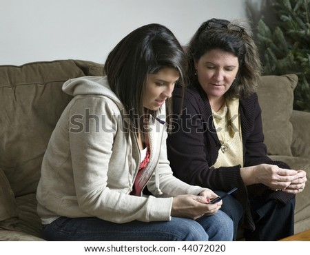 Mother watches over her daughter as she text messages a friend