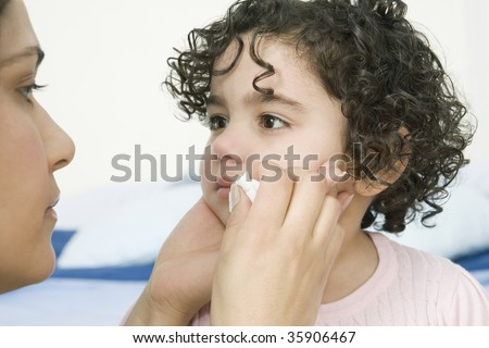 Mother wiping child's tears