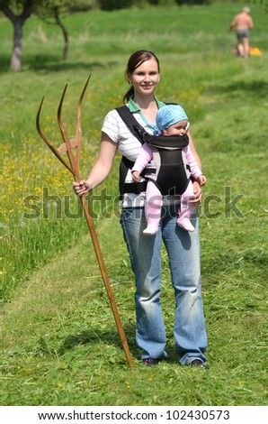mother with a baby on a stretcher cutting the grass