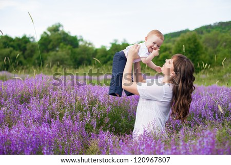 Mother with a cute baby posing sitting on a field of purple flowers around.