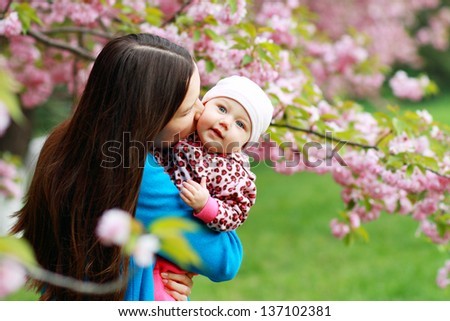 Mother with baby at outdoors in spring blooming garden