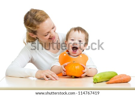 Mother with baby at the table. Boy holding pumpkin