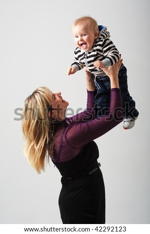 mother with baby boy on a gray background