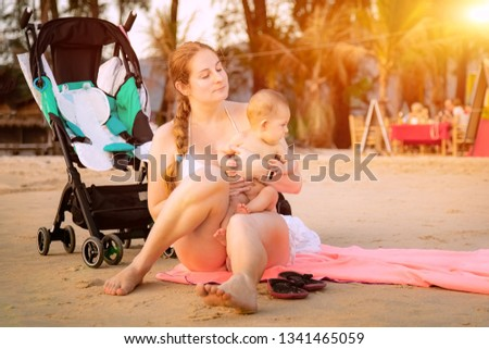 Mother with baby daughter on the beach. They are sitting on a towel and take sunbathing. Stroller staying near them on a sand. Infant sit on mom. #1341465059